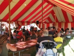 Folks gather to listen to a speaker at one of the X Tents.