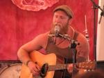 Gabriel Kelley with guitar, harmonica, and beard.